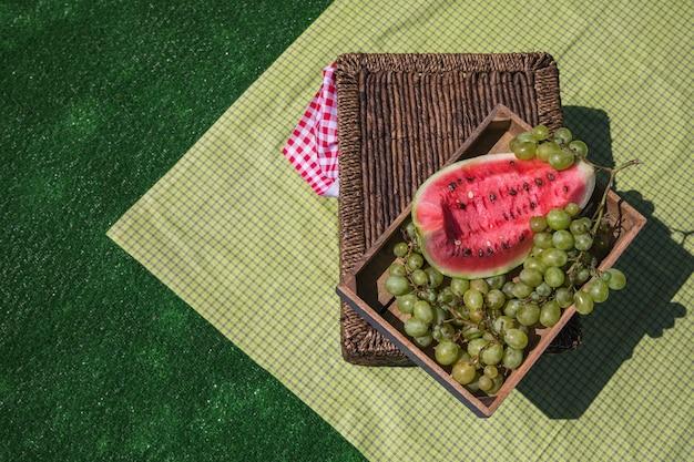 Een bovenaanzicht van watermeloen en druiven kist op picknickmand