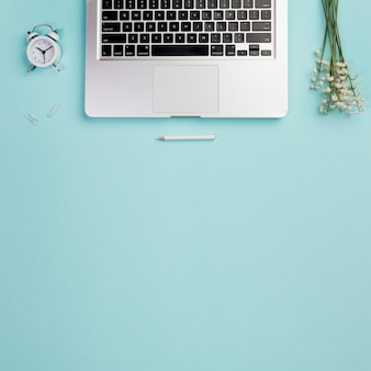 Een bovenaanzicht van wekker, potlood met laptop en lelietje-van-dalen op blauwe bureau