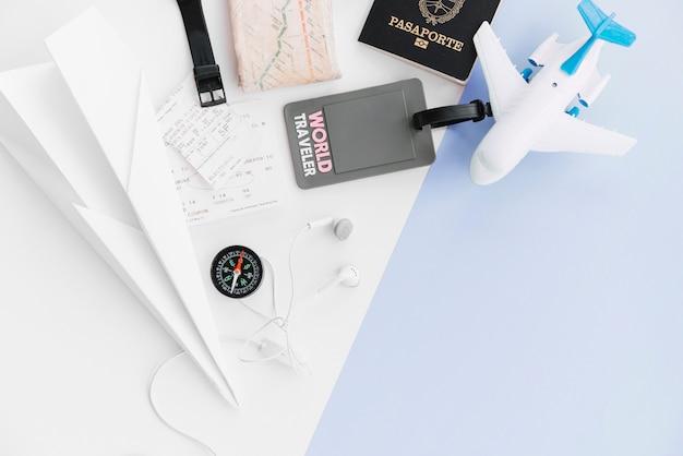 Een bovenaanzicht van wereldreizigerslabel met paspoort; papieren vliegtuig; kaart; kompas; kaartjes; speelgoedvliegtuig en oortelefoon op dubbele achtergrond