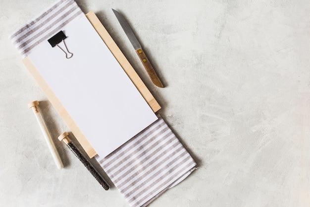 Een bovenaanzicht van witboek op klembord met mes; reageerbuisjes voor servetten en kruiden