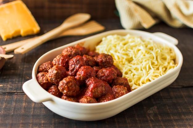 Een bovenaanzicht van witte lunchbox gevuld met gehaktballen en trenette pasta