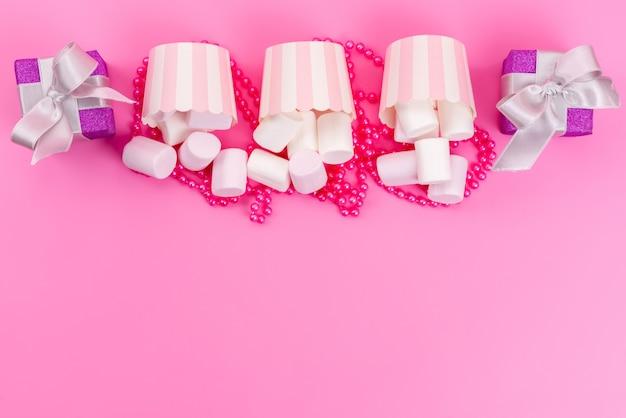 Een bovenaanzicht van witte marshmallows in papieren verpakkingen samen met kleine paarse geschenkdozen op roze bureau, zoete cake meringue