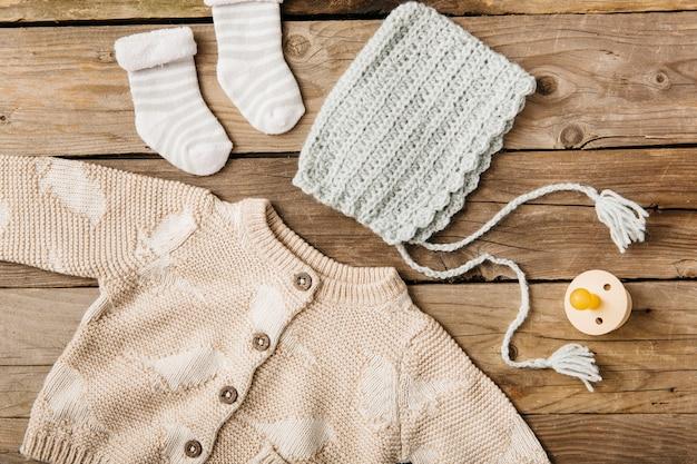 Een bovenaanzicht van wollen baby's kleding met fopspeen op houten tafel