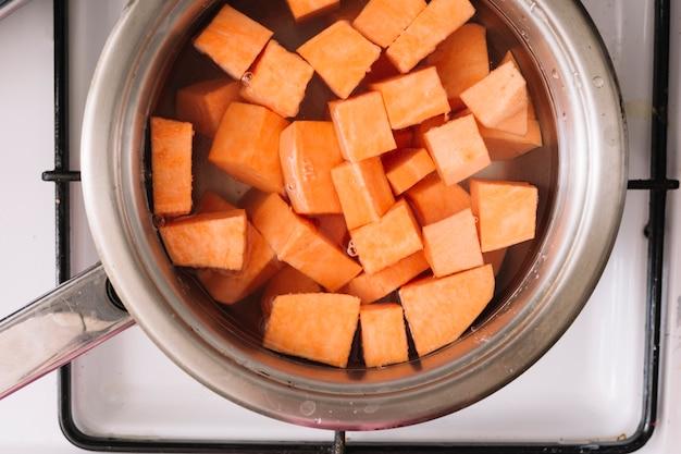Een bovenaanzicht van zoete aardappelen plak koken in de metalen pan op gas