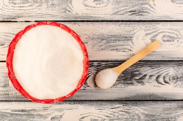 Een bovenaanzicht veel zout binnen rode ronde plaat met houten lepel op het grijze bureau