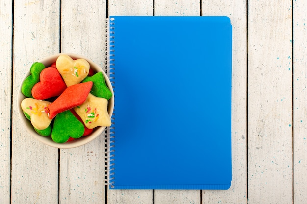 Een bovenaanzicht veelkleurige heerlijke koekjes verschillend gevormd binnen plaat met blauw schrift op het grijze oppervlak