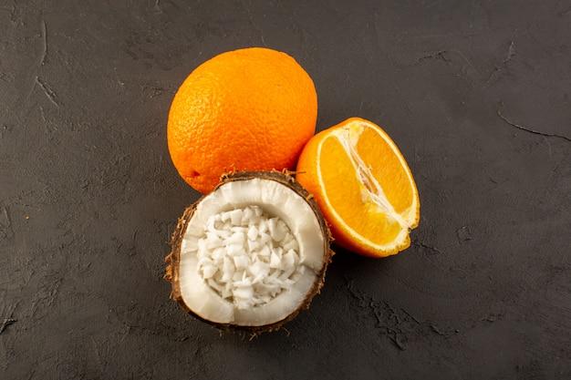 Een bovenaanzicht vers oranje, sappig geheel en gesneden zachte vruchten samen met gesneden kokosnoot op het donkere achtergrondcitrusvruchtensap