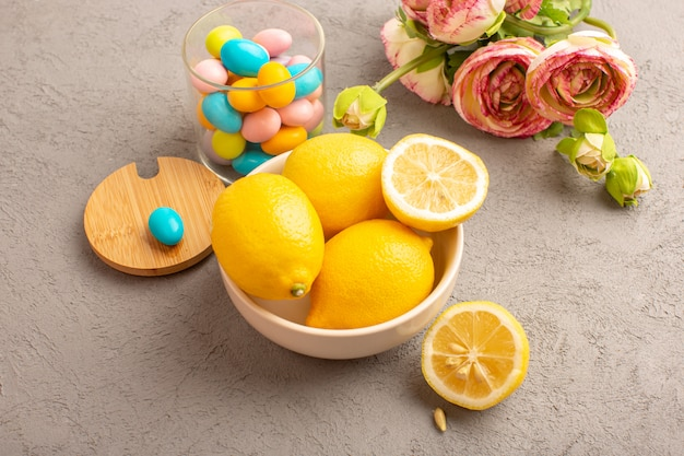 Een bovenaanzicht verse citroenen zuur rijp geheel met kleurrijke snoepjes gedroogde bloemen zachte citrus tropische vitamine geel op de crème balie