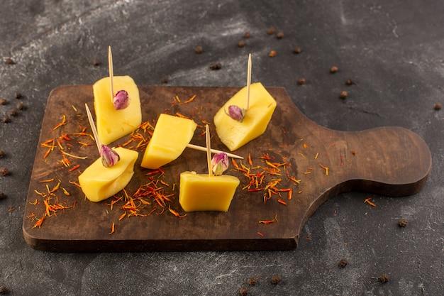 Een bovenaanzicht verse gele kaas met bruine koffiezaden op de grijze koffie van de de maaltijdsnack van het bureauvoedsel