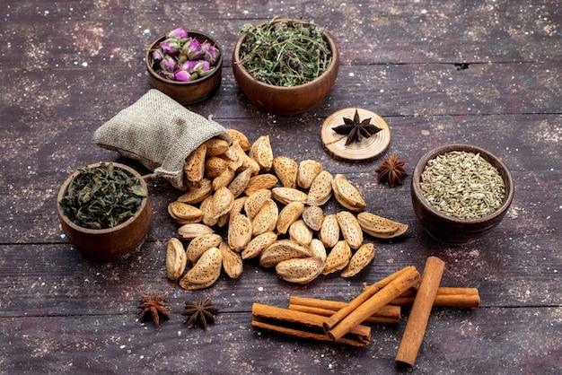 Een bovenaanzicht verse noten gezouten en smakelijk samen met kaneel op de donkere houten de snackschaal van de bureaunoot