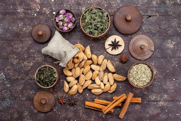 Een bovenaanzicht verse noten gezouten en smakelijk samen met kaneel op de donkere houten noten van de de snackshell van de bureaunoot