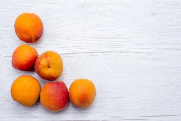 Een bovenaanzicht verse perziken rijp en zacht op de witte achtergrond fruit kleur vers