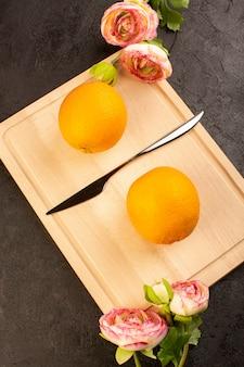 Een bovenaanzicht verse sinaasappelen zure rijp geheel met gedroogde rozen zachte citrus tropische vitamine geel op het donkere bureau