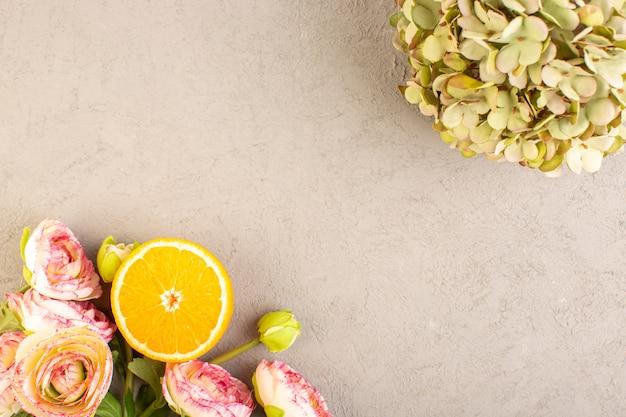 Een bovenaanzicht verse sinaasappelen zure rijp gesneden en hele zachte citrus tropische vitamine geel samen met gedroogde bloemen op de crème bureau
