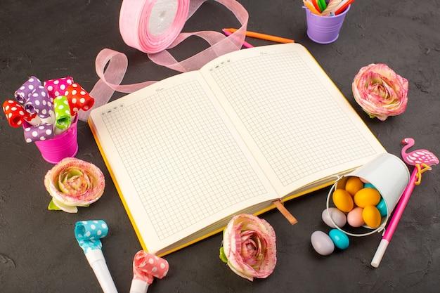 Een bovenaanzicht voorbeeldenboek en bloemen samen met snoepjes en decoraties op het donkere bureau