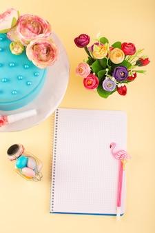 Een bovenaanzicht voorbeeldenboek en cake met bloemen op de gele kleur van de de verjaardagsviering van de bureaucake