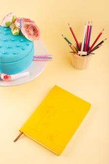 Een bovenaanzicht voorbeeldenboek en cake met veelkleurige potloden op de gele kleur van de de cakekleur van de bureauverjaardag