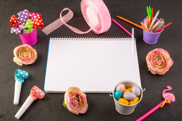 Een bovenaanzicht voorbeeldenboek en snoepjes samen met bloemenkaarsen en potloden op het donkere suikergoed van de de fotodecoratie van de bureaukleur