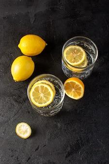 Een bovenaanzicht water met verse citroen koel drankje met gesneden citroenen in transparante glazen op de donkere achtergrond cocktail drinken fruit