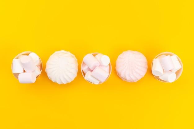 Een bovenaanzicht witte marshmallows heerlijk en smakelijk in papieren verpakkingen op geel bureau, suiker zoet banket