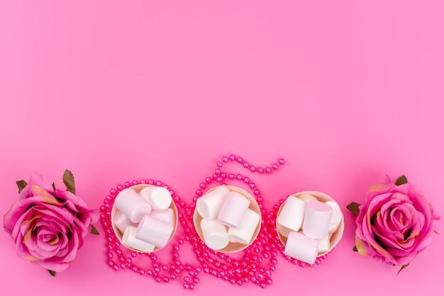 Een bovenaanzicht witte marshmallows in papieren verpakkingen samen met roze rozen op roze bureau, suikerzoete banketbakkerij