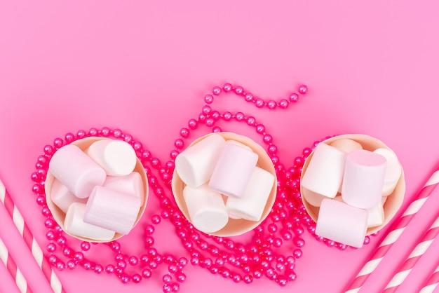 Een bovenaanzicht witte marshmallows in roze papieren verpakkingen samen met rietjes op roze zoete suikersnoepjes