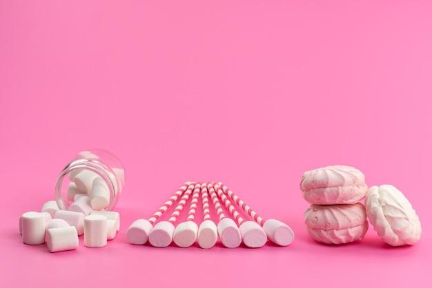 Een bovenaanzicht witte marshmallows met roze stokjes samen met schuimgebak op roze bureau, suikerzoete kleur