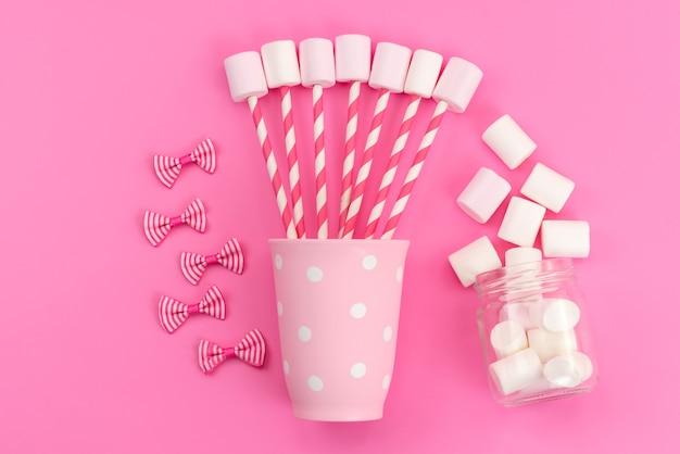 Een bovenaanzicht witte marshmallows met roze stokken en strikken op roze bureau, suikerzoete kleur