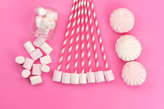 Een bovenaanzicht witte marshmallows met schuimgebak op roze bureau, suikerzoete kleur