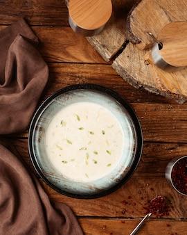 Een bovenaanzicht yoghurt soep in zwarte plaat op de houten bureau maaltijd maaltijdsoep