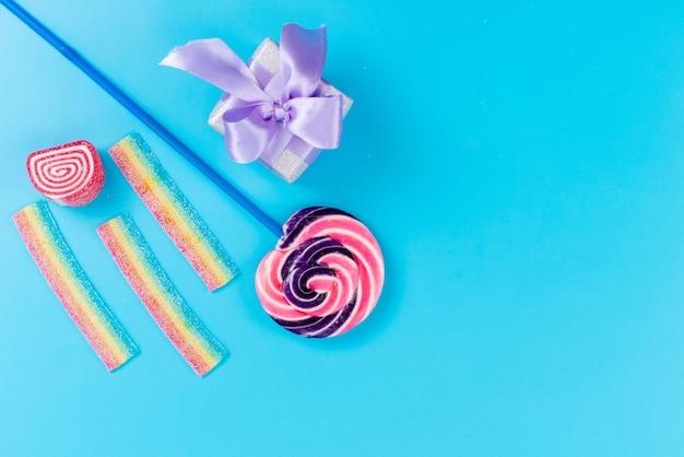 Een bovenaanzicht zoete lolly met blauwe stok en kleine paarse geschenkdoos op blauw bureau, zoete suikerverjaardag