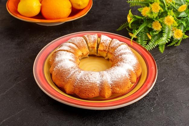 Een bovenaanzicht zoete ronde cake met suikerpoeder gesneden zoete heerlijke geïsoleerde cake binnen plaat samen met citroenen en grijze achtergrond biscuit suiker koekje
