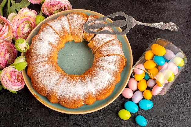 Een bovenaanzicht zoete ronde cake met suikerpoeder samen met kleurrijke snoepjes gesneden zoete heerlijke geïsoleerde cake binnen plaat en grijze achtergrond koekje suiker koekje