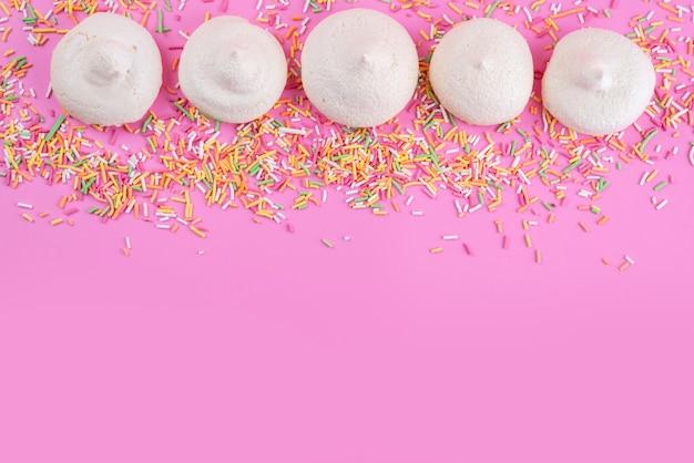 Een bovenaanzicht zoete schuimgebakjes met kleurrijke snoepjes op roze bureau, koekjescake suikerzoet