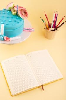 Een bovenaanzichtcake en voorbeeldenboek met veelkleurige potloden op het gele de cakepartij van de bureauverjaardag cleberation