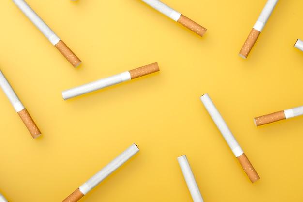 Een bovenste afbeelding van verschillende sigaretten. plat leggen. sigaretten op geel.