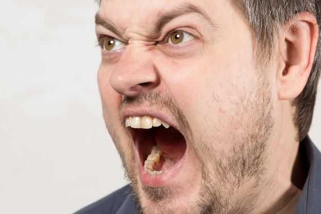 Een boze agressieve man schreeuwt met open mond.
