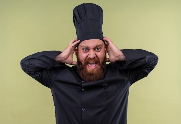 Een boze, bebaarde chef-kok in zwart uniform schreeuwt met handen op het hoofd terwijl hij op een groene muur kijkt