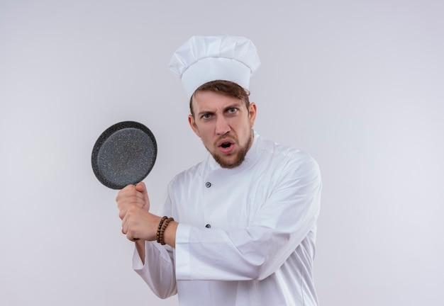Een boze, bebaarde chef-kokmens die een wit fornuisuniform draagt en een hoed die een pan houdt als een honkbalknuppel op een witte muur