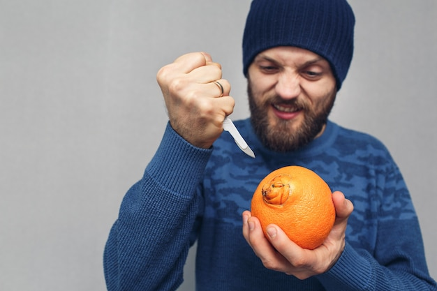 Een boze, bebaarde man wil met een scalpel de navel van een sinaasappel uitsnijden. concept van problemen als gevolg van aambeien.