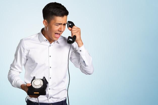 Een boze en geïrriteerde jongeman gilt tegen de telefoonhoorn