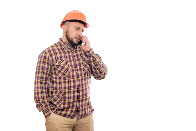 Een boze en nerveuze arbeider met een oranje helm praat luid aan de telefoon, schreeuwt in de telefoon. geïsoleerde witte achtergrond