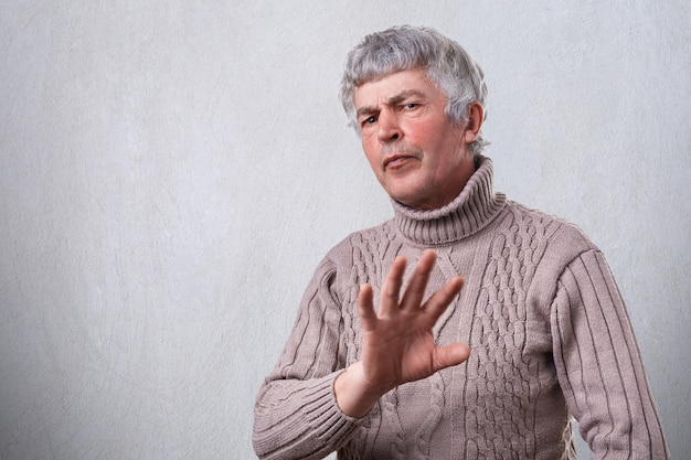 Een boze fronsende volwassen mens die negatieve uitdrukking heeft die weigert teken met palm toont