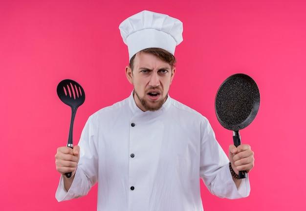 Een boze jonge, bebaarde chef-kok in wit uniform houdt een koekenpan en een zwarte lepel met gleuven vast terwijl hij op een roze muur kijkt