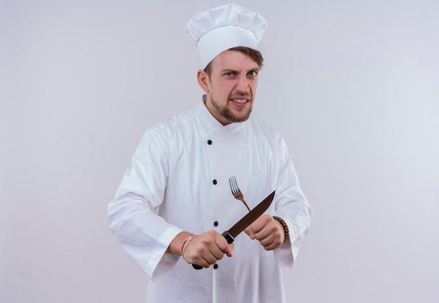 Een boze jonge, bebaarde chef-kokmens die een wit fornuisuniform draagt en een hoed met mes en vork in x-teken terwijl hij op een witte muur kijkt