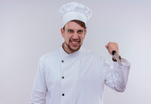 Een boze jonge, bebaarde chef-kokmens die een wit fornuisuniform draagt en een mes houdt terwijl hij op een witte muur kijkt