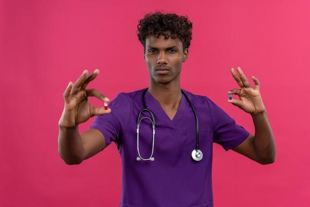 Een boze jonge knappe donkere arts met krullend haar die violet uniform draagt met een stethoscoop die pillen houdt