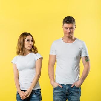 Een boze jonge vrouw die haar droevige vriend tegen gele achtergrond bekijkt