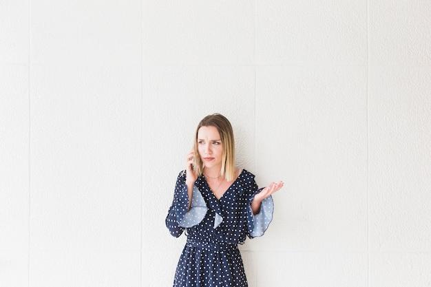 Een boze jonge vrouw die zich voor muur bevindt die op mobiele telefoon spreekt