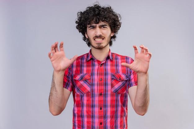 Een boze knappe man met krullend haar in een geruit overhemd die een klauwgebaar doet als een kat